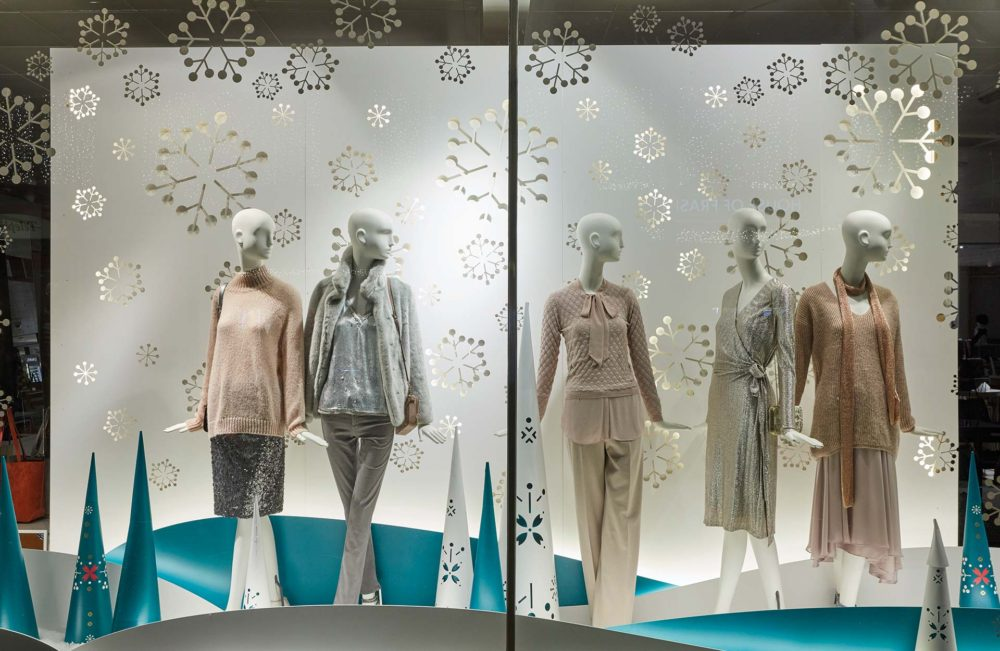 shop window display with snowflake decal decorations and female mannequins