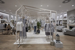 visual merchandising shop interior of The White Company displaying mannequins under wooden frame